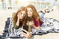 Two playful female friends taking a selfie on the beach - GIOF03034