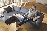 Senior man sitting on couch, using laptop - SBOF00459