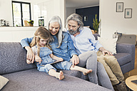 Grandparents and granddaughter sitting on couch, using tablet - SBOF00462