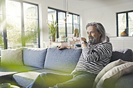 Senior man sitting on couch, talking into smartwatch - SBOF00465