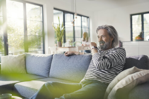 Senior man sitting on couch, talking into smartwatch - SBOF00465