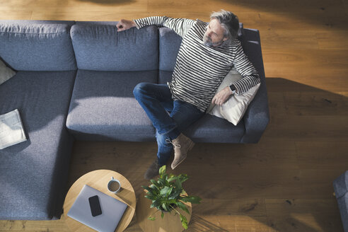 Senior man sitting on couch, relaxing and thinking - SBOF00468