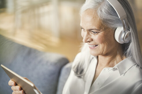 senior woman using digital tablet and headphones - SBOF00477