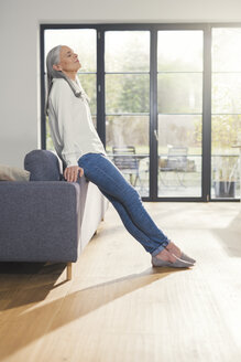 Senior woman standing by couch in living room, with eyes closed - SBOF00486