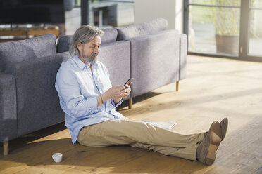Senior man using smartphone, sitting on floor - SBOF00489