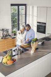 Happy senior couple preparing food in kitchen with online recipe - SBOF00495