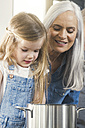 Grandmother and granddaughter cooking together, looking at pot - SBOF00507