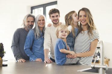 Happy family with grandparents and children standing in the kitchen - SBOF00516