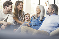 Extended family sitting on couch, smiling happily - SBOF00522