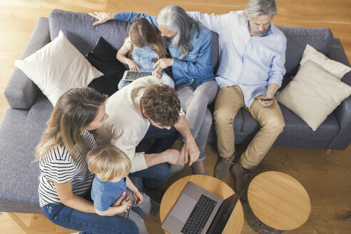 Extended family sitting on couch, using mobile devices - SBOF00525