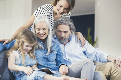 Family sitting on couch, watching granddaughter use tablet pc - SBOF00528