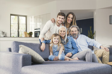 Extended family sitting on couch, smiling happily - SBOF00531