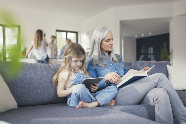 Grandmother and granddaughter sitting on couch, reading together book and tablet pc - SBOF00534 - Steve Brookland/Westend61