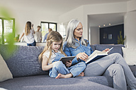 Grandmother and granddaughter sitting on couch, reading together book and tablet pc - SBOF00534