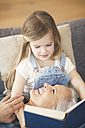 Grandmother and granddaughter sitting on couch, reading together a book - SBOF00537