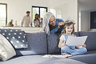 Grandmother playing with granddaughter, puuting crown on her head - SBOF00540