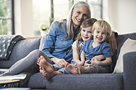 Grandmother sitting on couch with her grandchildren - SBOF00543