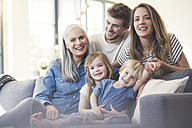 Extended family sitting on couch, smiling happily - SBOF00546