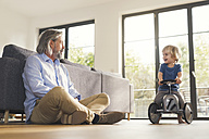 Grandfather playing with grandson, sitting on toy car - SBOF00552