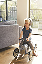 Happy blond boy playing on toy car - SBOF00555