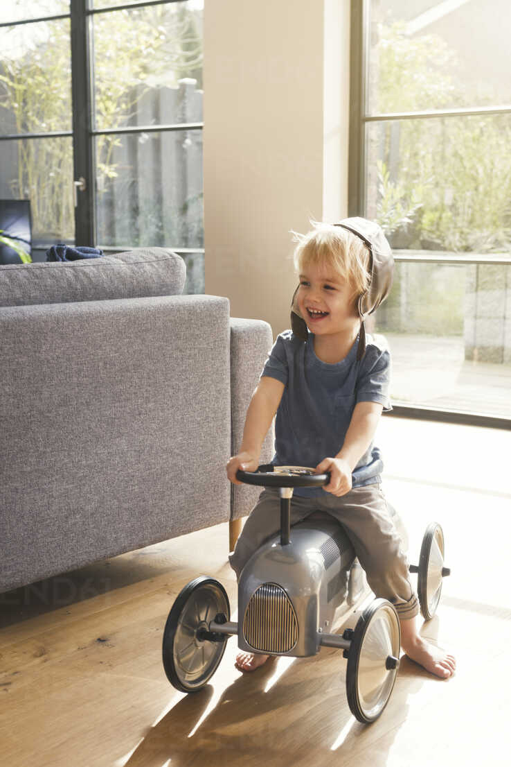 Happy blond boy playing on toy car - SBOF00555 - Steve Brookland/Westend61