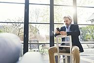 Senior businessman sitting on chair, using smartphone - SBOF00561