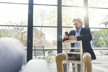 Senior businessman sitting on chair, using smartphone - SBOF00561