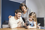 Parents watching daughter use a microscope, smiling proudly - SBOF00567