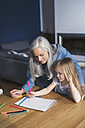 Grandmother and granddaughter making a drawing together - SBOF00570