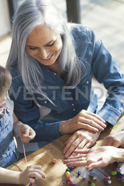 Grandmother and granddaughter and mother threading beads - SBOF00579 - Steve Brookland/Westend61