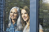 Mother and daughter looking out of window - SBOF00585
