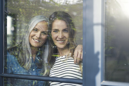 Mother and daughter looking out of window - SBOF00588