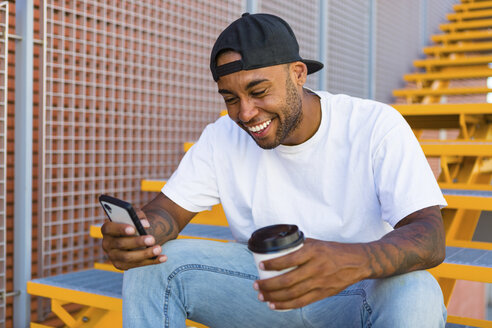 Laughing young man with coffee to go sitting on stairs looking at smartphone - MGIF00060
