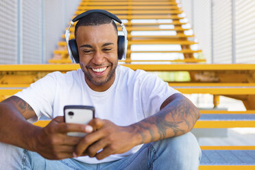 Portrait of laughing young man with headphones sitting on stairs looking at smartphone - MGIF00063