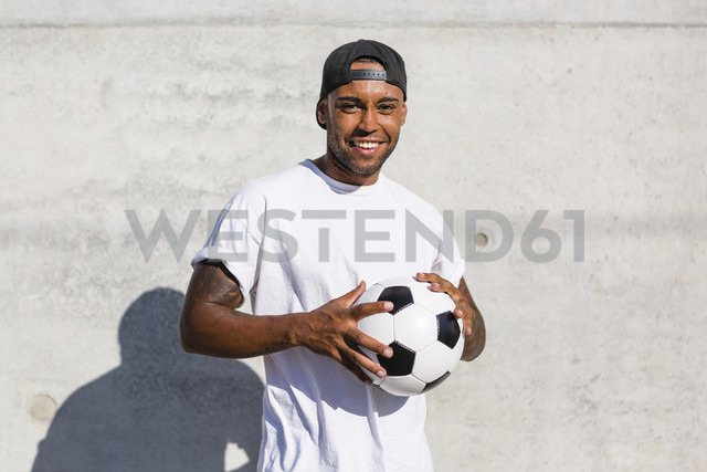 Portrait of smiling young man with soccer ball - MGIF00075 - Giorgio Magini/Westend61