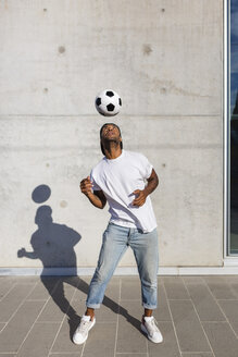Young man playing with soccer ball in front of concrete wall - MGIF00078