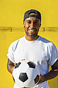 Portrait of smiling man with soccer ball in front of yellow wall - MGIF00081
