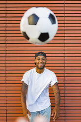 Portrait of laughing man having fun with soccer ball - MGIF00084