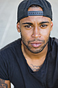 Portrait of serious young man with stubble wearing basecap - MGIF00093