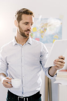 Bearded man in office with cup of coffee looking at tablet - GIOF03041
