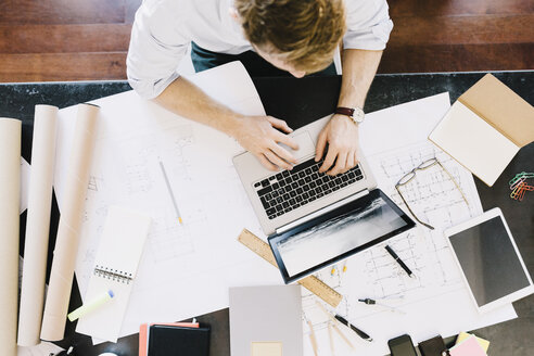 Man using laptop next to construction plan at desk, top view - GIOF03050