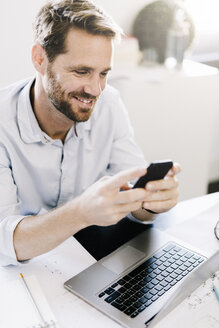 Portrait of smiling businessman using smartphone at desk in his office - GIOF03059