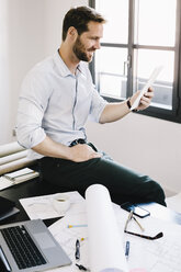 Architect sitting on desk in his office using tablet - GIOF03062