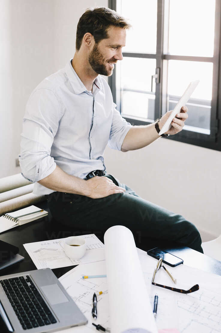 Architect sitting on desk in his office using tablet - GIOF03062 - Giorgio Fochesato/Westend61