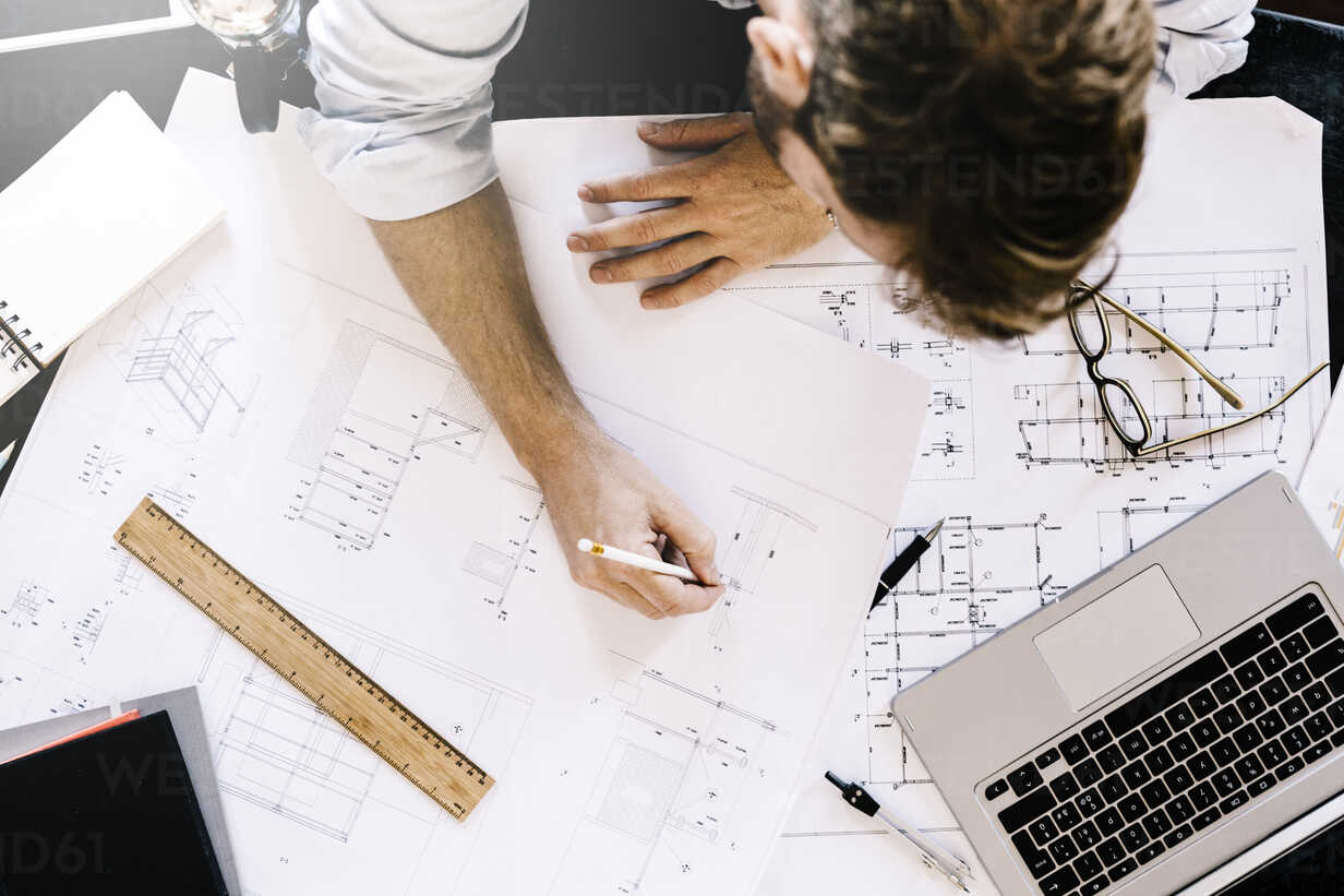 Man working on construction plan at desk, top view - GIOF03068 - Giorgio Fochesato/Westend61