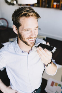 Portrait of smiling businessman using cell phone - GIOF03077
