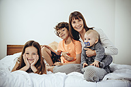 Happy mother in bed with her three children - MFF03692