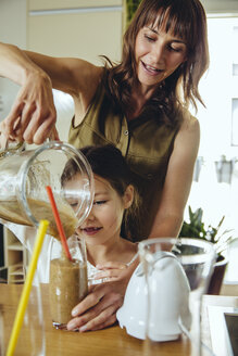 Girl pouring smoothie into glass with mother's help - MFF03698