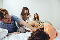 Parents and their children having a pillow fight in bed - MFF03707