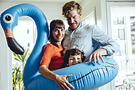 Happy parents with son holding an inflatable flamingo at home - MFF03710